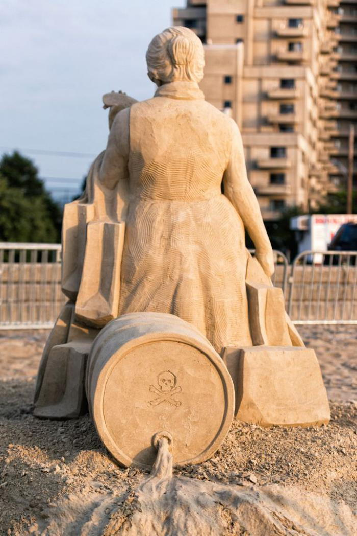 Sand sculpture-cum-sociale-messaggio-on-the-Кonsumgesellschaft