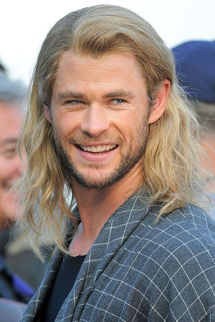 Chris Hemsworth cu păr lung blond și barbă neagră la un eveniment